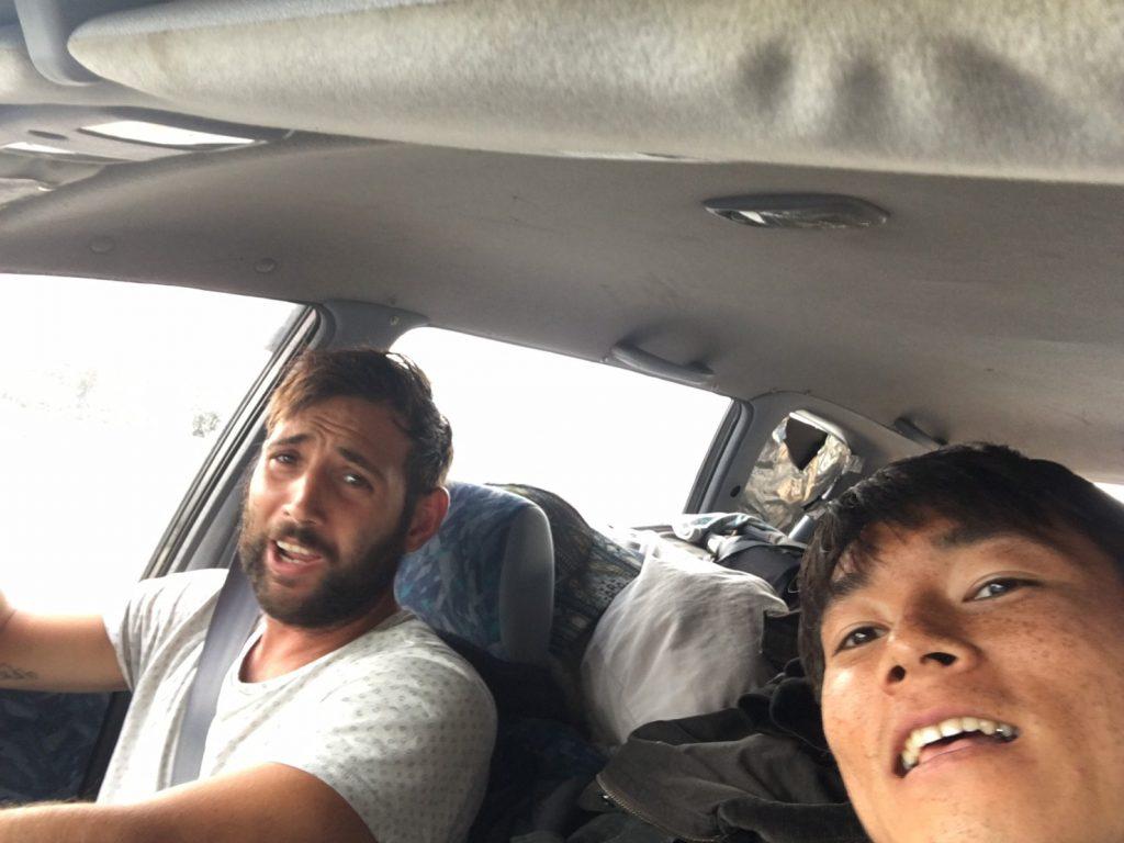 外国人と日本人2人が車で写真を撮っている。